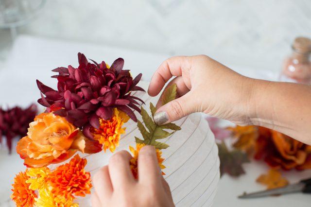 Lem daun pada lentera kertas secara acak di bawah bunga agar terlihat lebih menarik