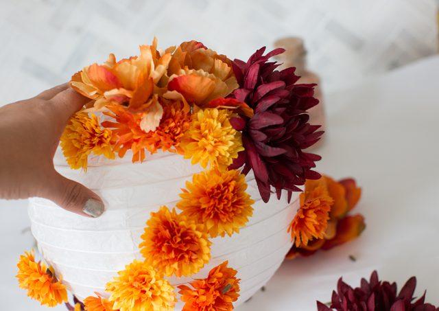 Tempelkan bunga secara teratur di sekitar lentera kertas